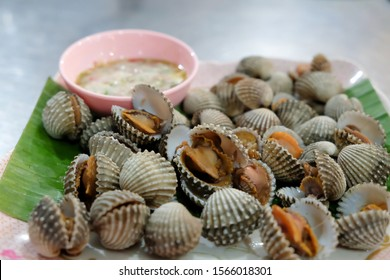 Fresh and delicious boiled cockles shell with spicy seafood sauce. Steamed cockle Boiled cockles with tasty sauce top view,thai food.