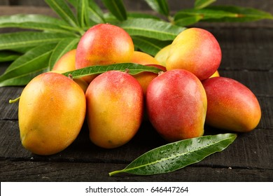 Fresh delicious sweet mangoes on a wooden background.
