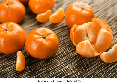 Fresh, delicious tangerines  in different conditions, peeled, unpeeled, sliced on the striped material, close up