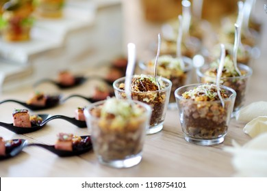 Fresh and delicious vegetable and pork salad served in mini glasses on a party or wedding reception. Plates with assorted fancy finger food snacks on an event party or dinner.