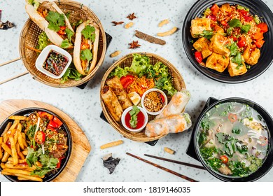 Fresh and delicius Vietnamese food table, Pho ga, pho bowls, noodles, spring rolls, asian dinner table on bright background