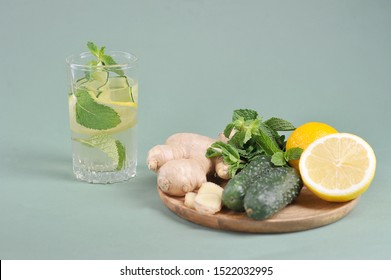 Fresh, detox drink water sassi. Ingredients for making a sassi drink: lemon, cucumbers, ginger root, mint on a round wooden tray. Light background.