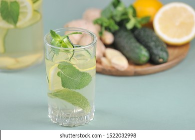 Fresh, detox drink water sassi. Ingredients for making a sassi drink: lemon, cucumbers, ginger root, mint on a round wooden tray. Light background. Close-up.
