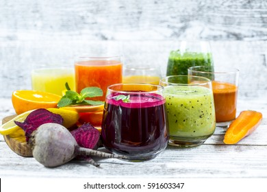 Fresh detox juices from fruit and vegetables in glass bottles on a wooden background