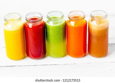 Fresh detox juices glass in row bottles on white background