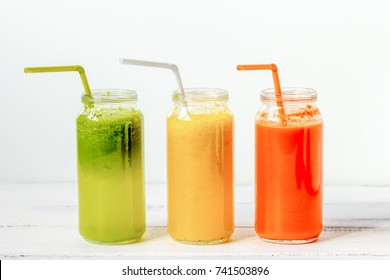 Fresh detox juices glass in row bottles on white background