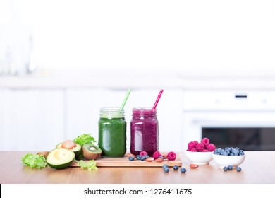 Fresh detox smoothie on table, green and berries cocktails in jar on kitchen interior, nobody