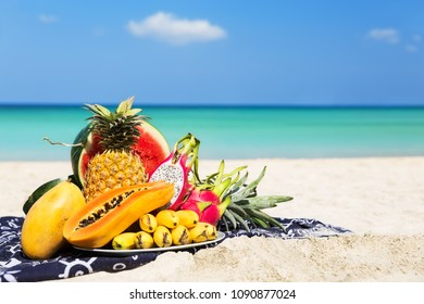 Fresh different tropical fruits placed on the plate with blue sky and sea as background. Summer time concept of healthy eating.
