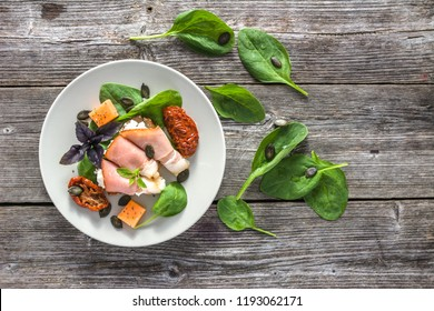 Fresh dish with italian antipasti on table. Food snack - ham prosciutto, cheese, basil and dry tomatoes. Appetizer on plate.
