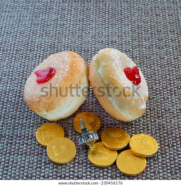 Fresh donuts, silver dreidel and chocolate coins for Hanukkah celebration.