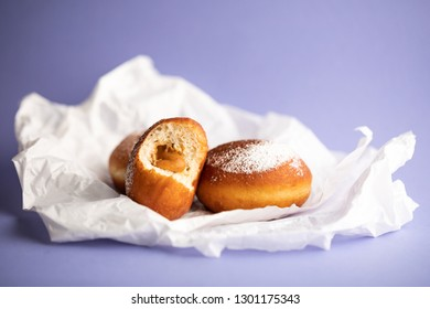 Fresh donuts sprinkled with powdered sugar and caramel sauce, closeup on a violet background. One donuts bitten. German donuts