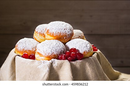 Fresh donuts (sufgania) with jam and dried cherries on a cotton material. Hanukkah holiday celebration and traditional jewish sweet