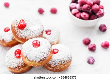 Fresh donuts (sufgania) with red jelly jam and fresh frozen cherries on a sugar powder background. Hanukkah holiday celebration and traditional jewish sweet