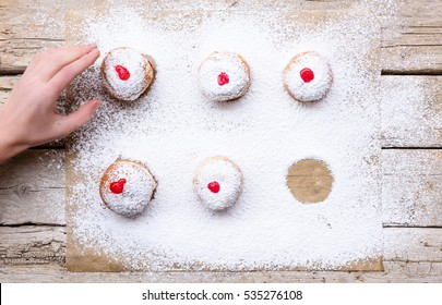 Fresh donuts (sufgania) with red jelly jam on a sugar powder and wooden background. Hand of woman taking donut from bakery paper. Hanukkah holiday celebration and traditional jewish sweet