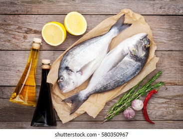 Fresh dorado fish cooking with spices and condiments on wooden table