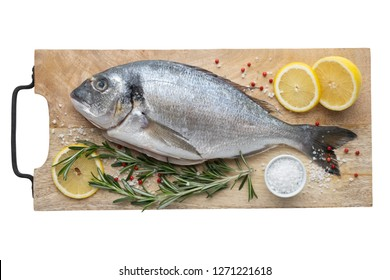 Fresh dorado fish with lemon slices, salt and rosemary on cutting board. Top view, isolated on white.