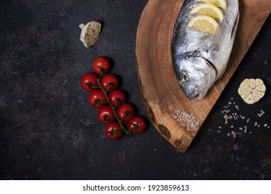fresh dorado fish on a wooden board. on a dark background. cooking with cherry tomatoes, olive oil, chili, garlic. dish of the Mediterranean diet