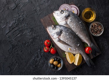 Fresh Dorado fish. Raw Dorado fish and ingredient for cooking. Fresh Dorado fish, Dorado with salt, tomatoes, olives on a wooden Board. The view from the top. Copy space