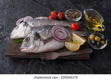 Fresh Dorado fish. Raw Dorado fish and ingredient for cooking. Fresh Dorado fish, Dorado with salt, tomatoes, olives on a wooden Board