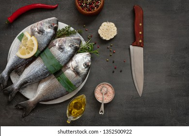 Fresh dorado fish, spices and olive oil on stone cutting board on dark table. Top view, copy space.