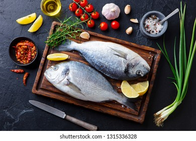 Fresh Dorado fishes on a wooden cutting board with vegetables, herbs and spices. Black stone background. Top view.