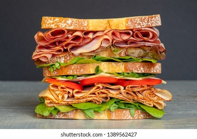 Fresh double layered sandwich with ham, lettuce, tomatoes, cheese on a toast bread. Food background. Close up. Very delicious sub sandwich. Fast food. Magazine cover.