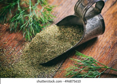 Fresh and dried dill on a wooden surface