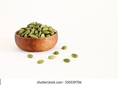 Fresh dried green cardamon seeds spice in a wooden bowl