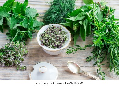 Fresh and dried herbs, lieves mix on wood table