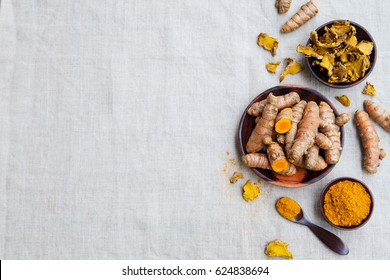 Fresh and dried turmeric roots in a wooden bowl. Grey textile background. Top view. Copy space.
