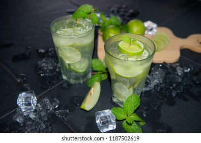 Fresh drink lime juice and slices with ice and peppermint leaves on black,Cold and refreshing detox water with lime and ice in glass,Fresh mojito cocktail with fresh lime and mint leaf,Copy space,