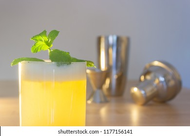 A fresh drink with mint garnish with stainless steel shaker, jigger and top.