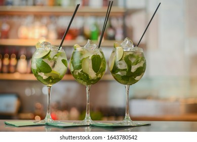 Fresh drinks Mojito with lime and ice in three clear glasses on a table in bar with copy space. Summer seasonal cold drinks for party.