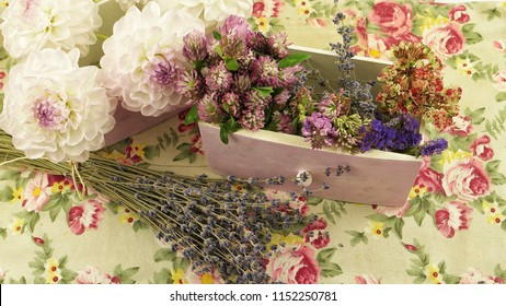 Fresh and dry flowers on the  fabric with floral pattern, floral arrangement