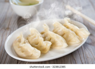 Fresh dumpling on plate. Chinese food with hot steams on old wooden background.