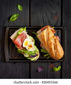 Fresh egg ham sandwich on dark board.