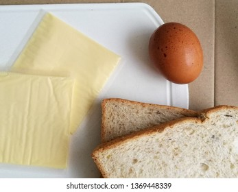 fresh Egg put near cheese and bread on white plate prepare for cook sandwich.