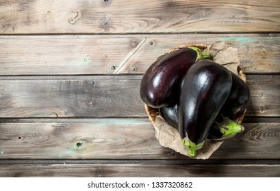 Fresh eggplant in the basket. On wooden background