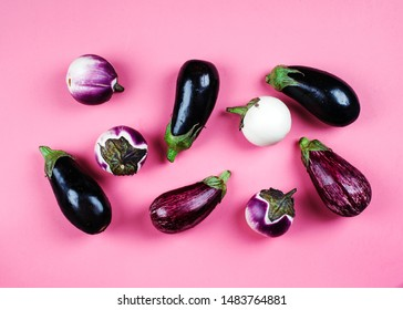 Fresh eggplants of different color and variety on a pink background, top view