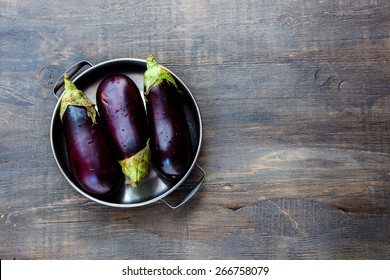 Fresh eggplants on dark wooden background.. Vegetarian food, health or cooking concept.