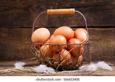 fresh eggs in a basket on wooden table.
