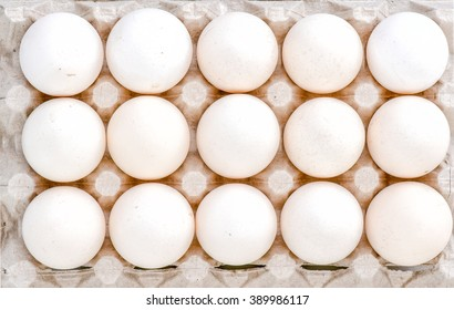 Fresh Eggs in paper egg box on White Background top view of eggs. Eggs in paper tray isolated on white Group of fresh eggs in a paper tray