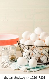 Fresh eggs rest in a wire basket with a vintage bowl and wire whisk, accented with old-fashioned salt and pepper shakers sitting ready for preparing breakfast.