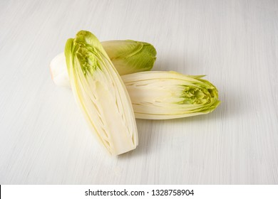 Fresh Endive or Chicory (Cichorium endivia) whole and halved on a white wooden table, copy space, selected focus