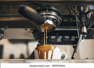 Fresh espresso coffee pouring through the bottomless portafilter in white ceramic cup and leaks away in artisan cafe shop Vintage professional coffee machine Unfocused black plate for your text behind
