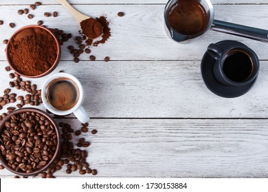 Fresh espresso cups, metal Turkish pot, roasted Arabica beans in clay bowls, ground coffee powder, spoon on while wooden table. Top view, copy space. Coffee shop, morning, baristas workplace  concept