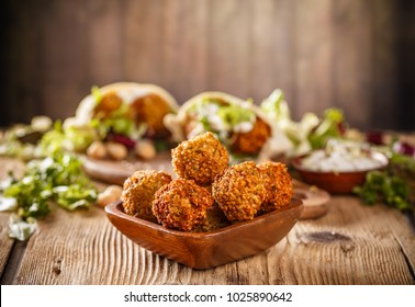 Fresh falafel balls on a wooden bowl