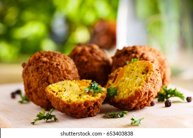 Fresh falafel balls on a wooden cutting board