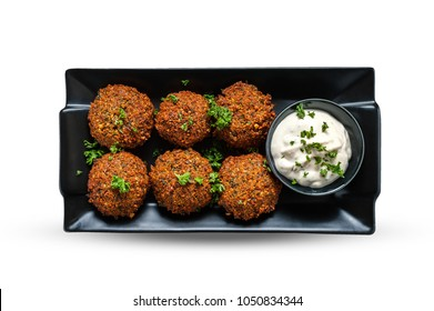 Fresh falafel with parsley and tzatziki sauce in black plate. Isolated on white background with clipping path.