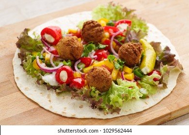 fresh falafel wrap with veggies, ready to roll